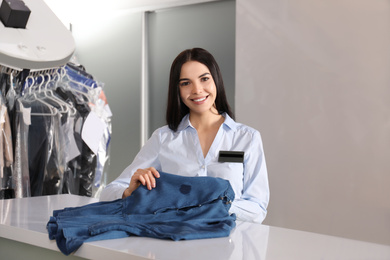 Female worker with stained clothes at dry-cleaner's