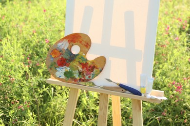 Wooden easel with blank canvas and painting equipment in meadow. Space for text
