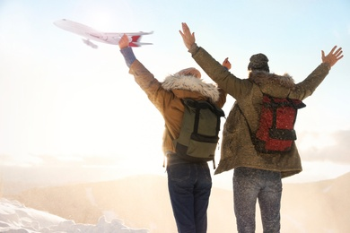 Excited couple in mountains under sky with flying airplane. Winter vacation