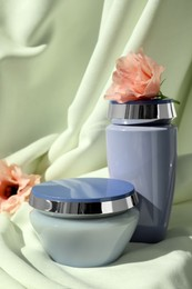 Hair care cosmetic products and beautiful flowers on light green fabric