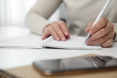Left-handed woman writing in notebook at table indoors, closeup
