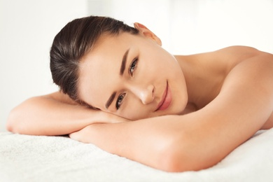 Young woman lying on massage table in spa salon