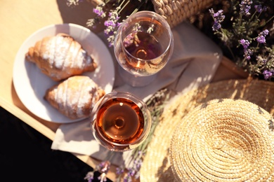 Plate with croissants and glasses of wine on wooden tray in lavender field, top view