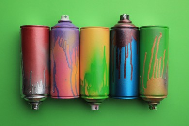 Used cans of spray paints on green background, flat lay. Graffiti supplies