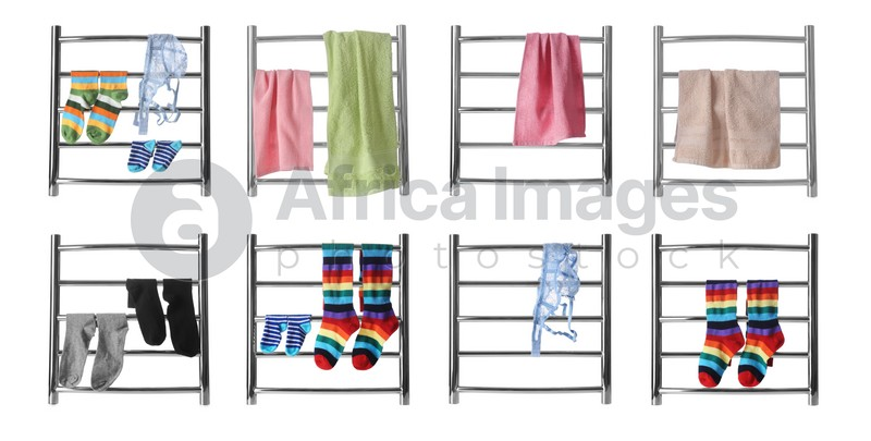 Set with modern heated towel rails with clothes and towels on white background