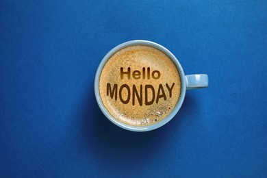 Hello Monday, start your week with good mood. Cup of freshly brewed aromatic coffee on blue background, top view