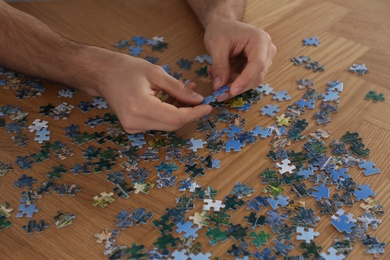 Man playing with puzzles at wooden table, closeup