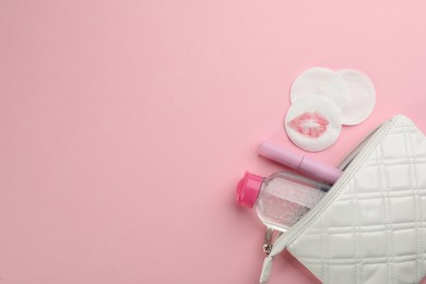 Clean and dirty cotton pads, cleansing water with mascara in bag on light pink background, flat lay. Space for text