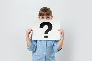 Girl holding sheet of paper with question mark on white background