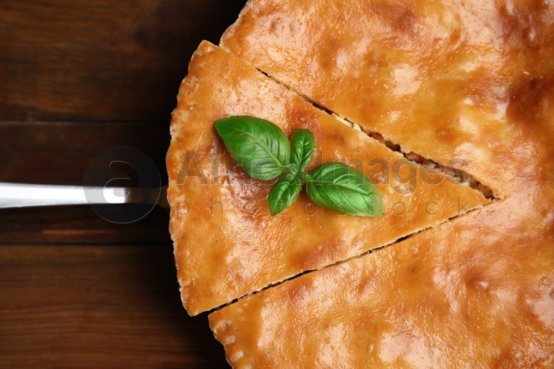 Delicious pie with meat and basil on wooden table, top view