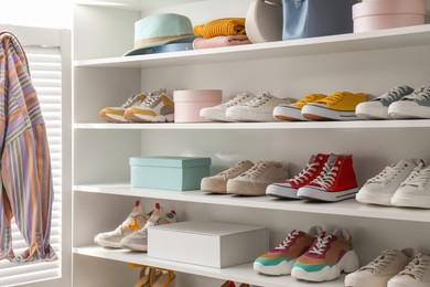 White shelving unit with collection of colorful sneakers and accessories indoors