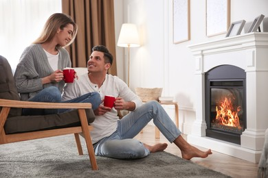 Happy couple with cups of hot drink resting near fireplace at home
