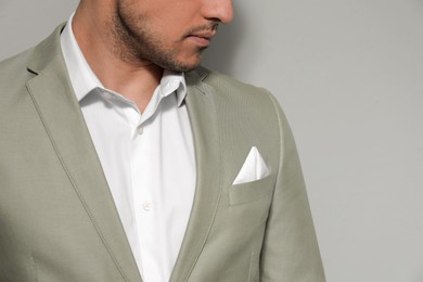 Man with handkerchief in breast pocket of his suit on grey background, closeup