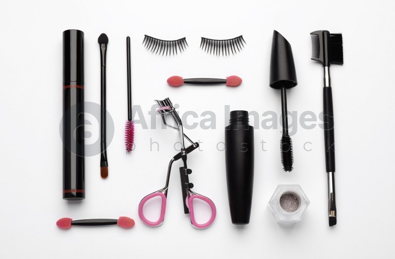 Composition with eyelash curler, makeup products and accessories on white background, top view