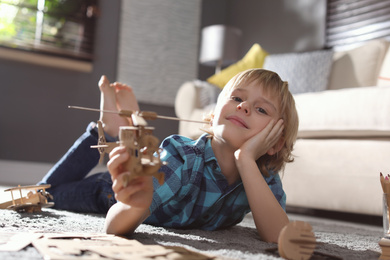 Little boy playing with cardboard helicopter on floor at home. Creative hobby