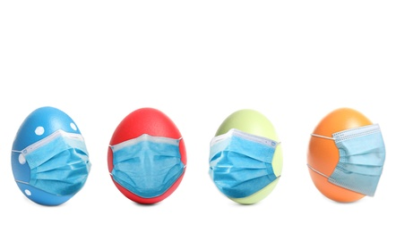 COVID-19 pandemic. Colorful Easter eggs in protective masks on white background