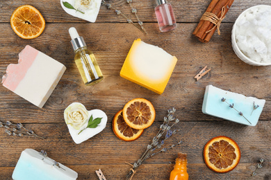 Flat lay composition with natural handmade soap and ingredients on wooden table