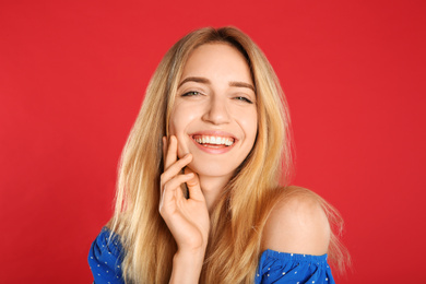 Portrait of beautiful young woman with blonde hair on red background
