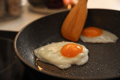Frying pan with cooked eggs on stove, closeup