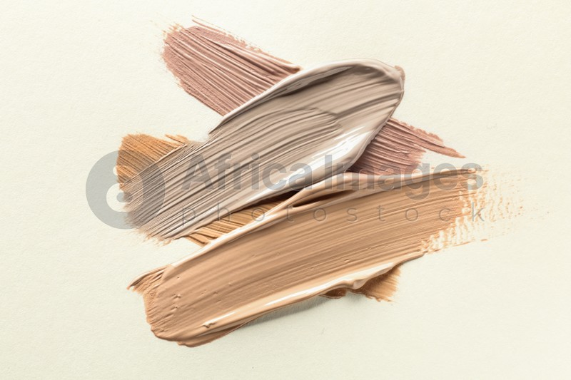 Different shades of liquid foundation on beige background, top view
