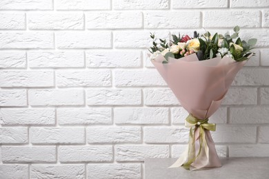 Beautiful bouquet with roses on light table near white brick wall. Space for text