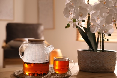 Beautiful orchid, teapot and cup with hot tea on table indoors