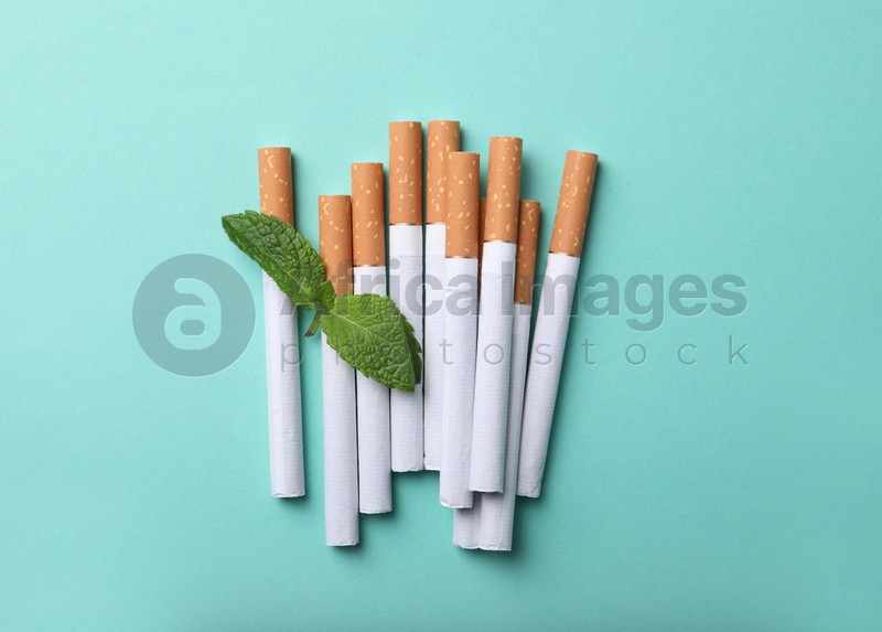 Menthol cigarettes and mint on turquoise background, flat lay