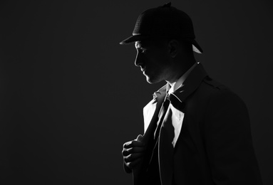 Old fashioned detective in hat on dark background, black and white effect. Space for text