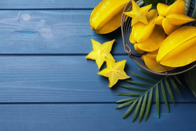 Delicious carambola fruits on blue wooden table, flat lay. Space for text