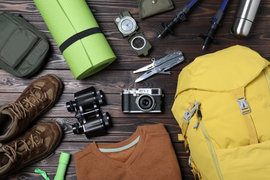 Flat lay composition with backpack and other camping equipment for tourism on wooden background