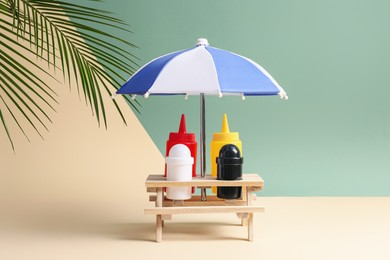 Wooden holder with different sauces, spices and toy umbrella on color background