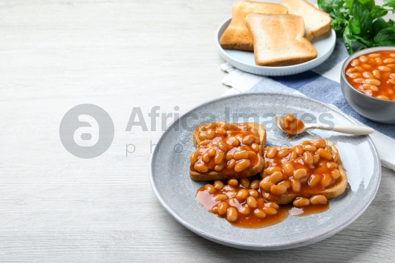 Toasts with delicious canned beans on white wooden table, space for text