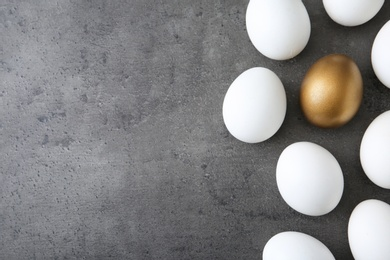 Flat lay composition with golden egg and others on grey background. Space for text