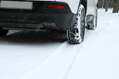 Car leaving tire tracks on snowy road outdoors