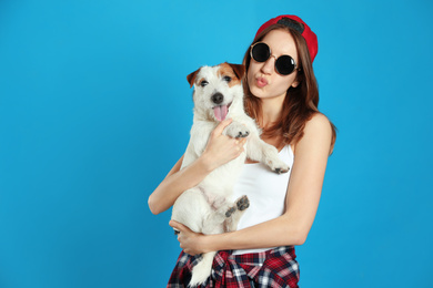 Young woman with her cute Jack Russell Terrier on light blue background. Lovely pet