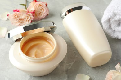 Hair care cosmetic products and flowers on light grey marble table
