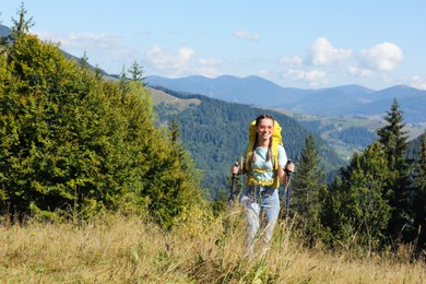Woman with trekking poles hiking in mountains