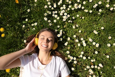 Happy woman listening to audiobook while lying on grass among blooming daisies, top view