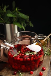 Tasty hot cranberry tea and fresh ingredients on wooden table
