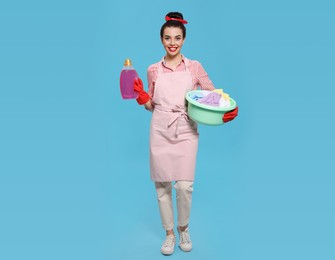 Housewife holding bottle of cleaning product and basin with clothes on light blue background