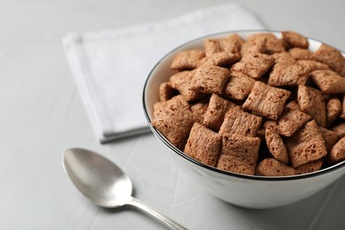Sweet crispy corn pads in bowl and spoon on light table, closeup