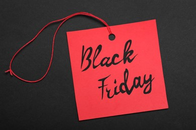Black Friday red tag on color background, top view