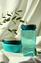Hair care cosmetic products and green leaves on light fabric