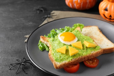 Halloween themed breakfast served on black table, closeup. Tasty sandwich with fried egg