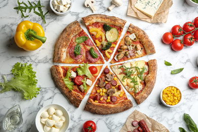 Flat lay composition with slices of different delicious pizzas on white marble table
