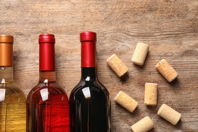 Flat lay composition with bottles of wine and corks on wooden table