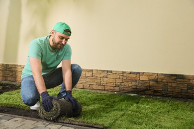Worker laying grass sod on ground at backyard, space for text