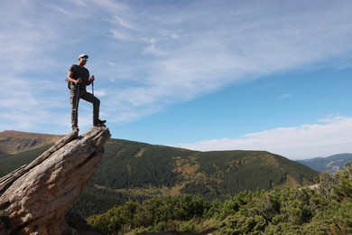 Man with backpack and trekking poles on rocky peak in mountains