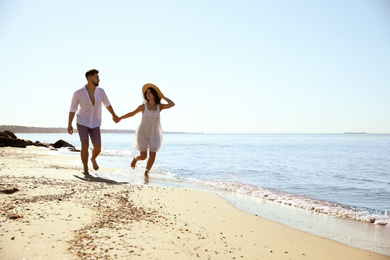 Happy young couple running on beach near sea. Honeymoon trip