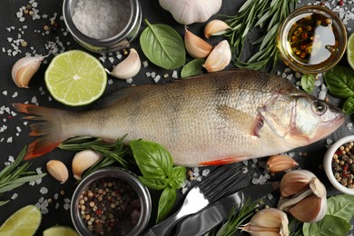 Fresh raw perch and ingredients on black slate table, flat lay. River fish